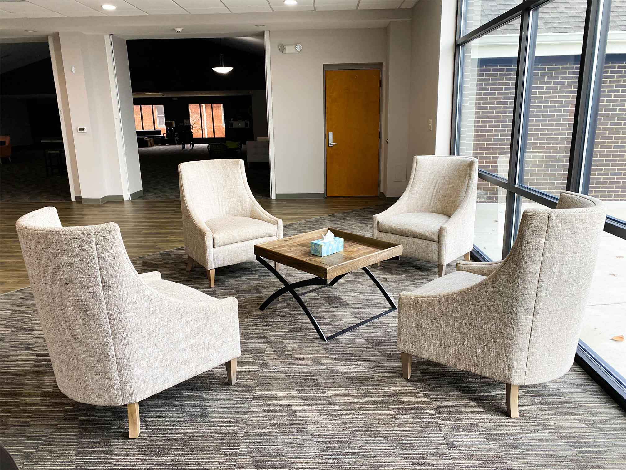 Four comfortable chairs in a circle by a big window in an airy room for counseling and therapy at New Hope Christian Church through ThrivePointe Counseling in Whitestown, IN 46075
