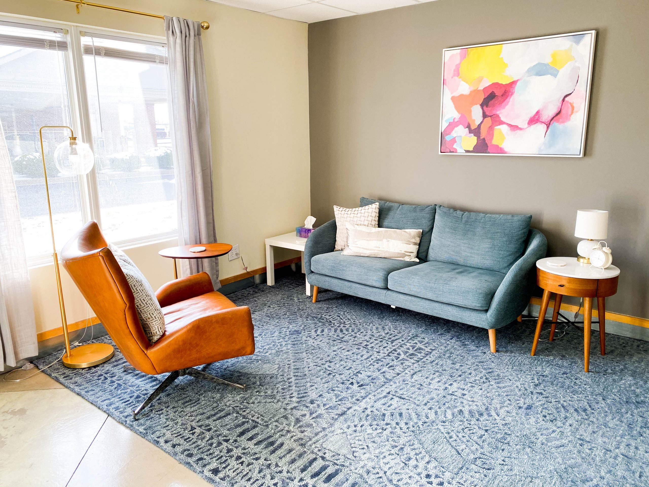 Room with a couch and chair facing each other with modern artwork and soft lighting for counseling with a ThrivePointe therapist in Fishers, IN. 46038