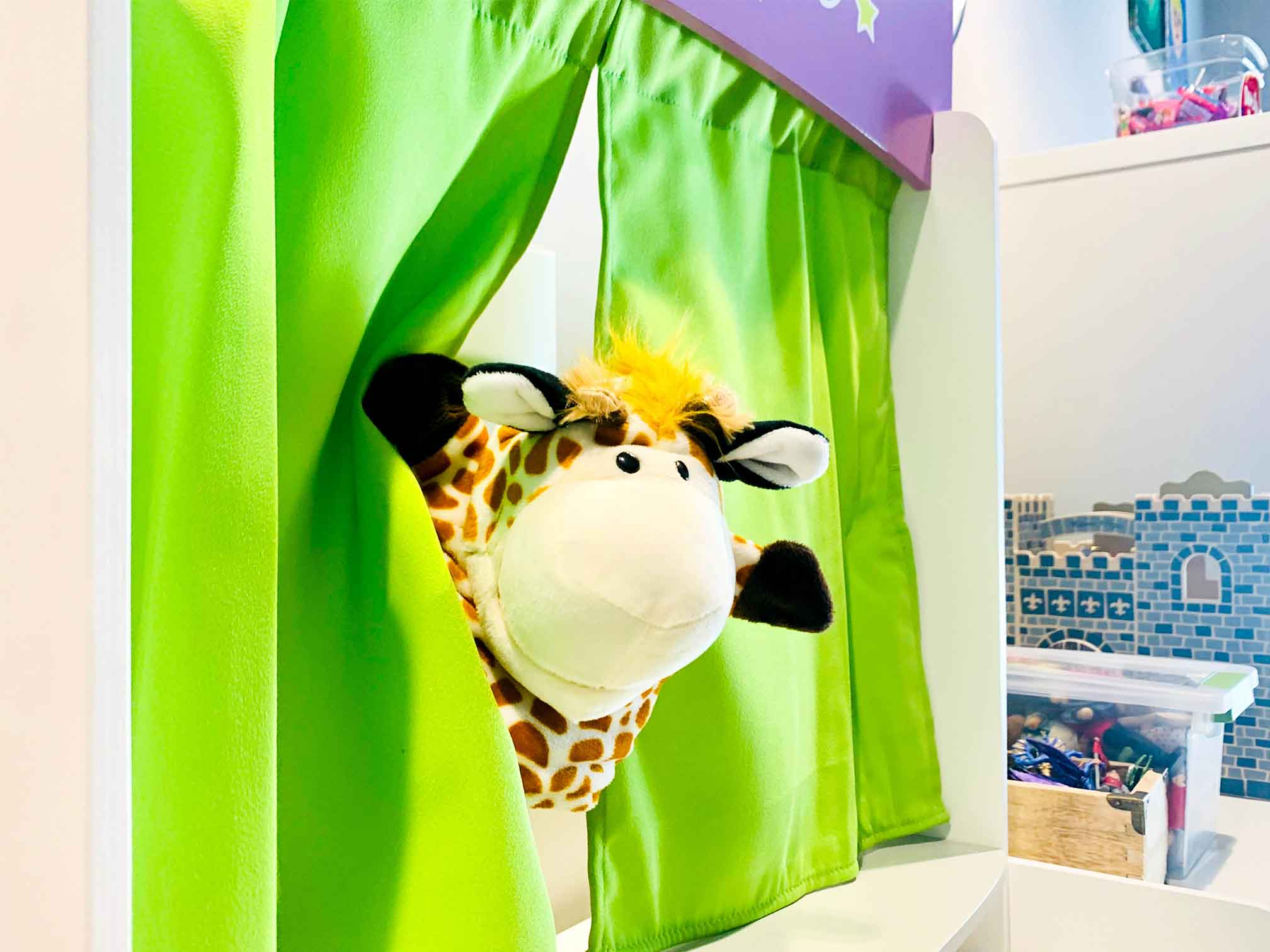 Puppet show with a giraffe poking through green curtains, looking happy in a beautifully decorated playroom for counseling and therapy. Your child can get help in play therapy in Ohio and Indiana for child counseling with ThrivePointe child therapists