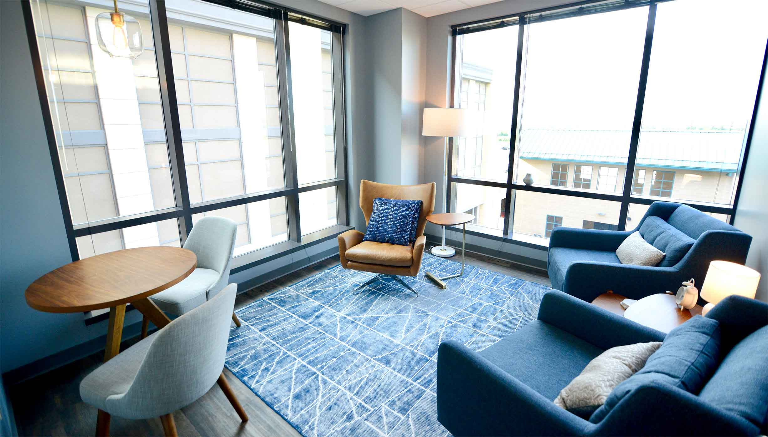 Brightly lit room with large windows and a welcoming setting with plush chairs and tables for a comfortable therapy feel in Liberty Center. ThrivePointe Counseling helps adults and children through therapy in Liberty Township, OH 45069