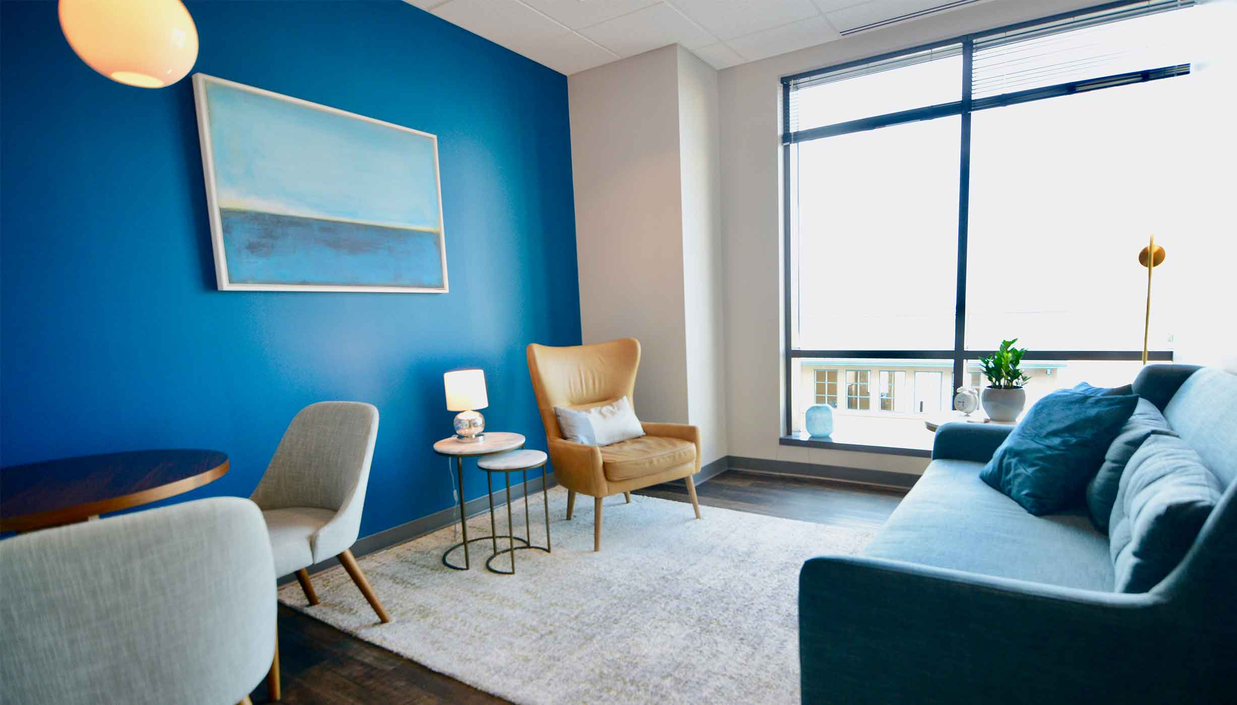 Brightly lit room with large windows and a welcoming blue wall with couch, chairs and tables, plants and modern art for a comfortable therapeutic feel in Liberty Center. ThrivePointe Counseling helps adults and children through therapy in Liberty Township, OH 45069