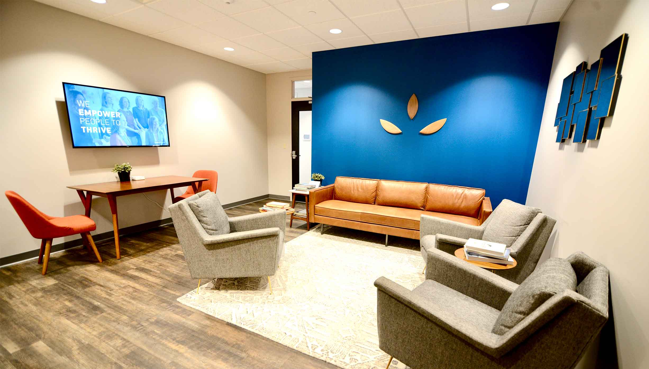 Comfortable and welcoming waiting room area with tables, chairs and couches, wooden and blue elements with rustic modern feel, petals or leaf parts on the wall for the ThrivePointe Counseling logo at Liberty Center office for therapy in Liberty Center, OH 45069